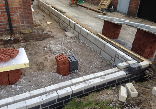Laying the first bricks on a wrap around extensions Crosby